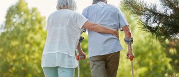 Senior mit Krückstock beim Gehen in der Reha im Garten